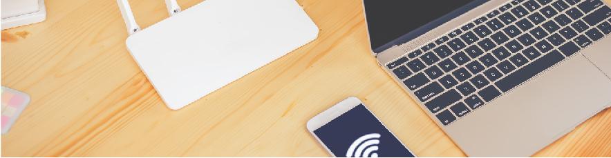 Auf dem Tisch befinden sich Router, Laptop und Smartphone